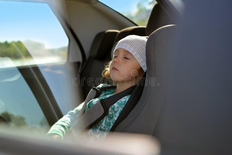 Behandla som ett barn platsen i bilen Lilla flickan sover i bilen royaltyfria bilder