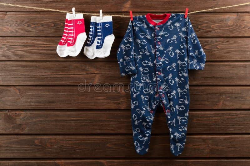 Behandla som ett barn pojkekläder & x28; sleepsuit och socks& x29; hänga på clotheslinen royaltyfri bild