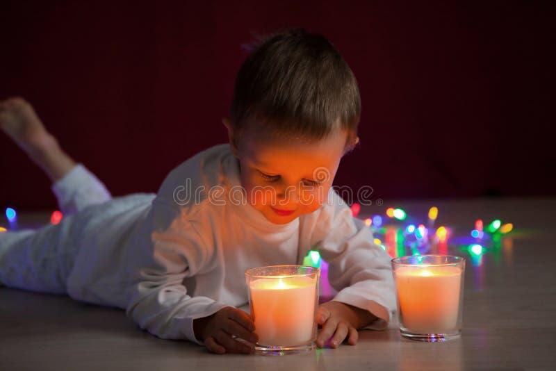 Behandla som ett barn pojkelögner i mörkret och blickar på branden av en julljus royaltyfria bilder