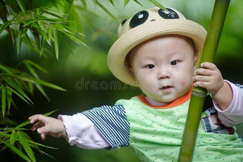 Behandla som ett barn pojkelek i bambuskog royaltyfria foton