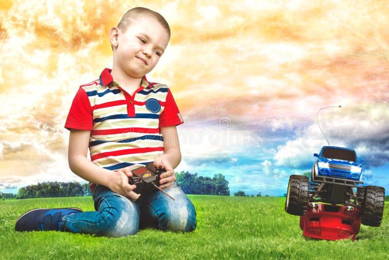 Behandla som ett barn pojkelekar med bilen på fjärrkontrollen Sitta på den gröna gräsmattan royaltyfri bild