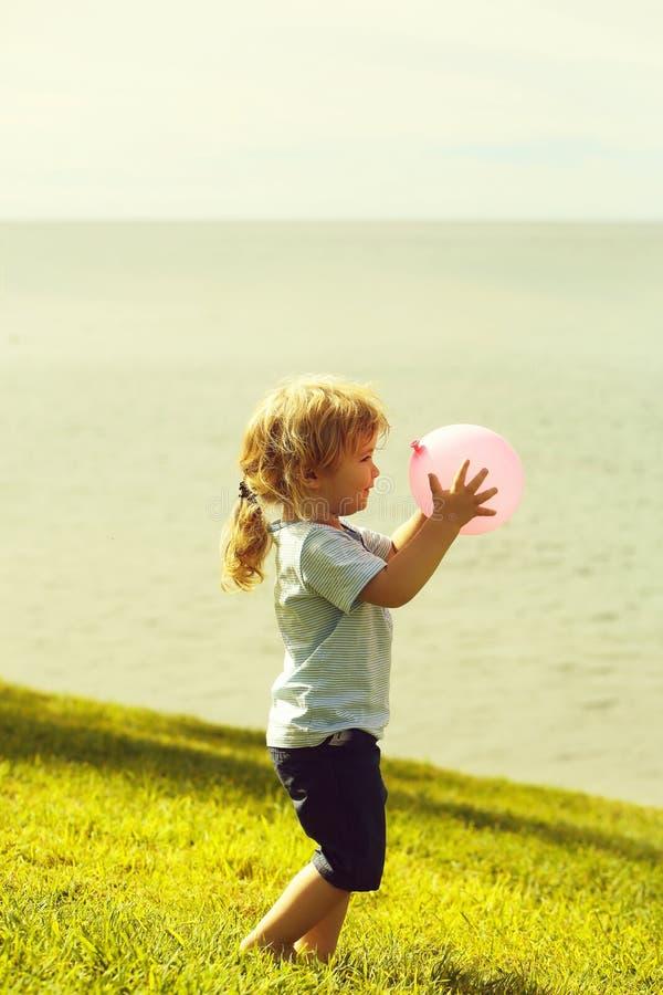 Behandla som ett barn pojkelekar med den rosa leksakballongen arkivbilder