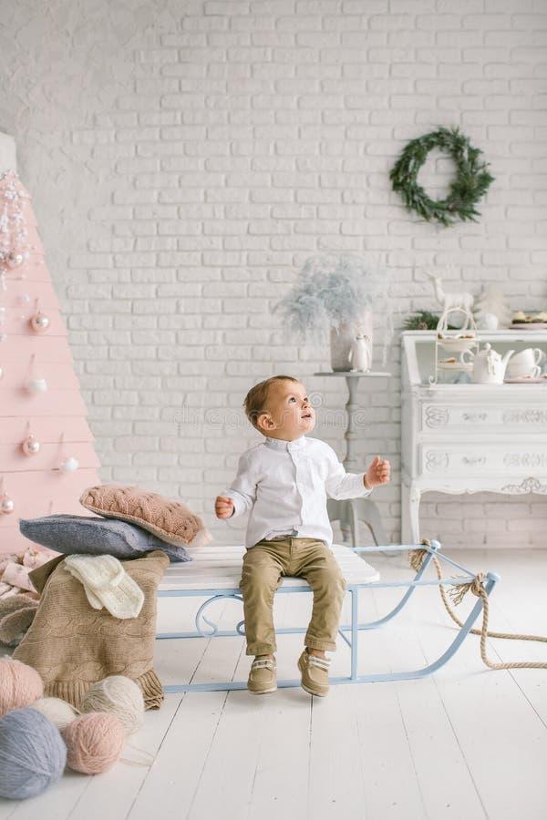 Behandla som ett barn pojken bara på släden som spelar den xmas dekorerade studion royaltyfria foton
