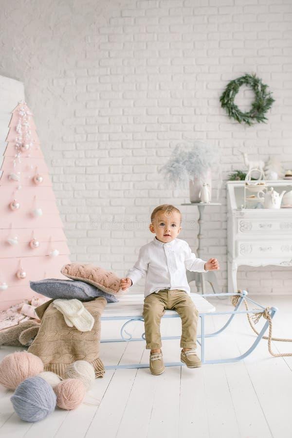 Behandla som ett barn pojken bara på släden som spelar den xmas dekorerade studion royaltyfri foto