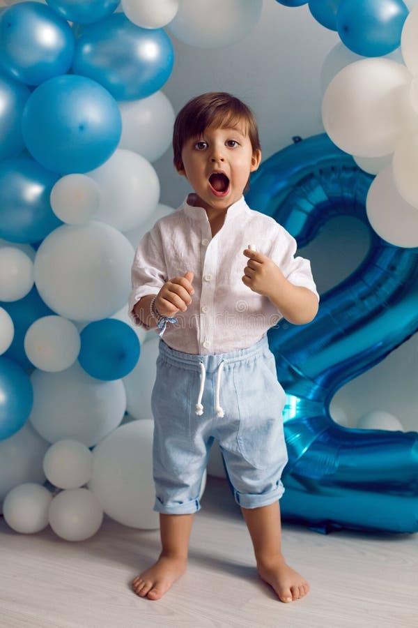 Behandla som ett barn pojken i blåa flåsanden och skjortaanseendet på golvet arkivbild