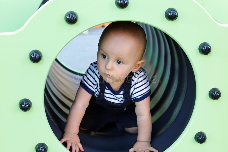 Behandla som ett barn pojken i en lekplatstunnel fotografering för bildbyråer