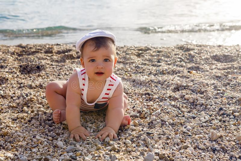 Behandla som ett barn pojken i hatt på strandkiselstenar arkivbilder