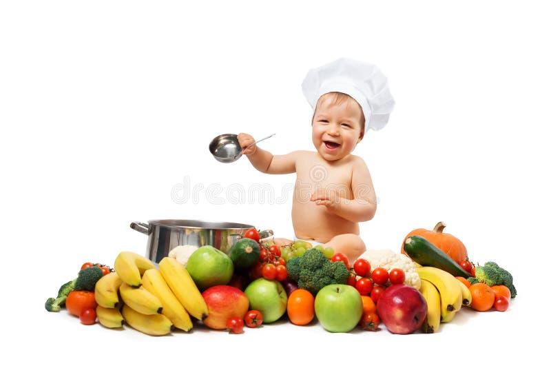 Behandla som ett barn pojken i kockhatt med matlagningpannan och grönsaker royaltyfri fotografi