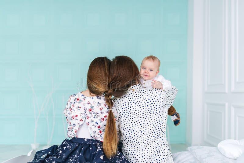 Behandla som ett barn pojken i vita pyjamasblickar över skuldra för fader` s, medan modern omfamnar honom arkivbild