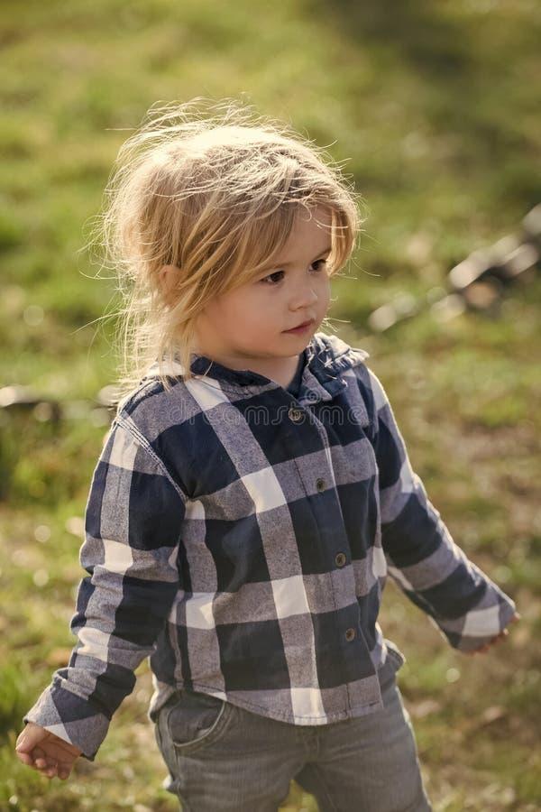 Behandla som ett barn pojken med blont hår i plädblåttskjortan, jeans royaltyfri fotografi