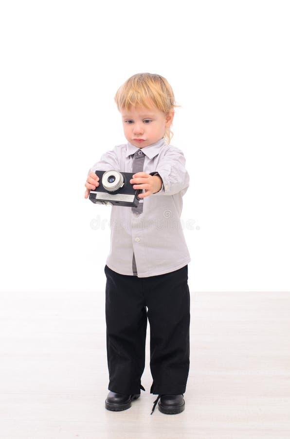 Behandla som ett barn pojken med en retro kamera i hand arkivfoto