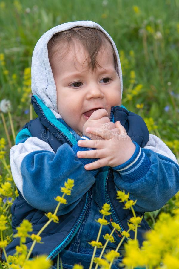 Behandla som ett barn pojken med huven sitter i naturen och lekarna med gr?set royaltyfria bilder