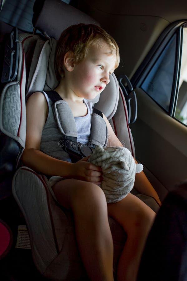 Behandla som ett barn pojken med ljust hårsammanträde i ett barnbilsäte med leksaken i händerna royaltyfri foto
