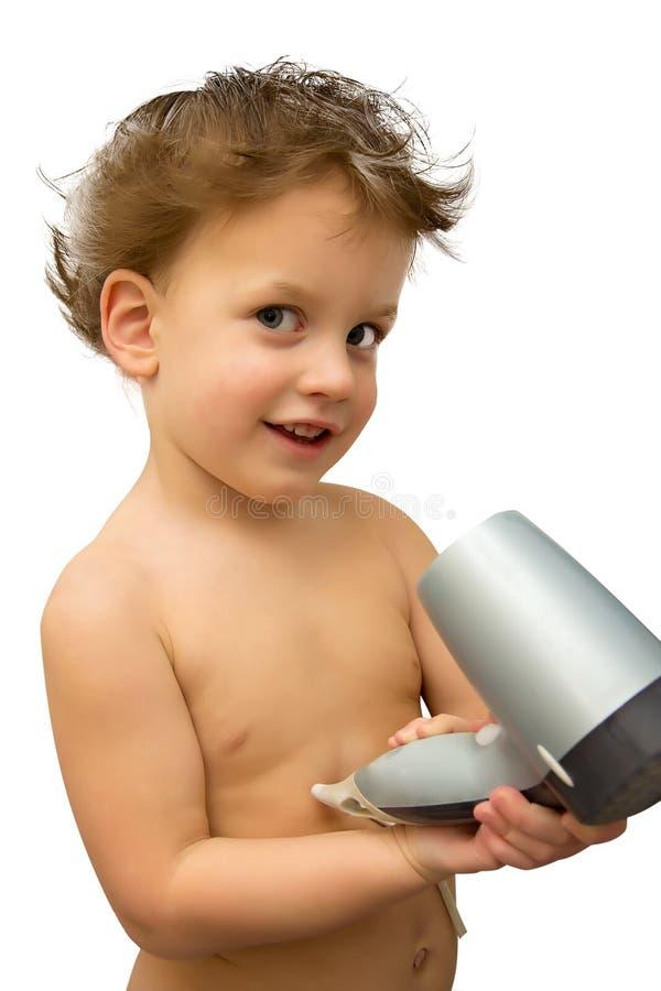 Behandla som ett barn pojken med hårtorken över vit arkivfoto