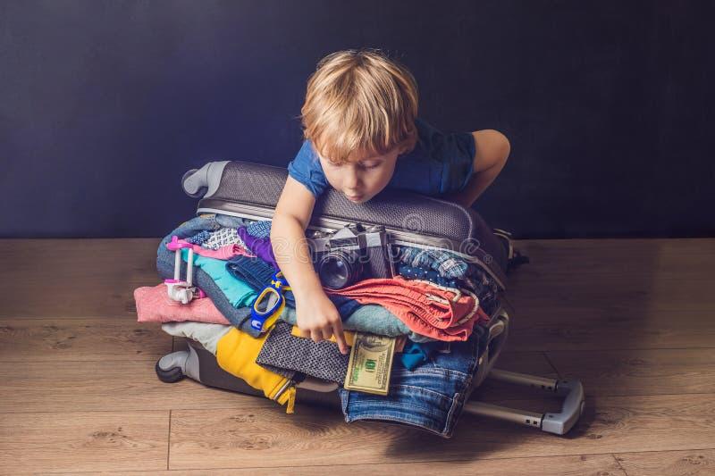 Behandla som ett barn pojken och loppresväskan Unge och bagage som packas för Vacatio fotografering för bildbyråer