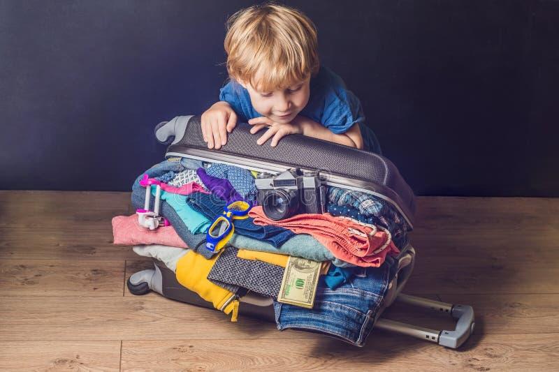 Behandla som ett barn pojken och loppresväskan Unge och bagage som packas för Vacatio arkivbilder