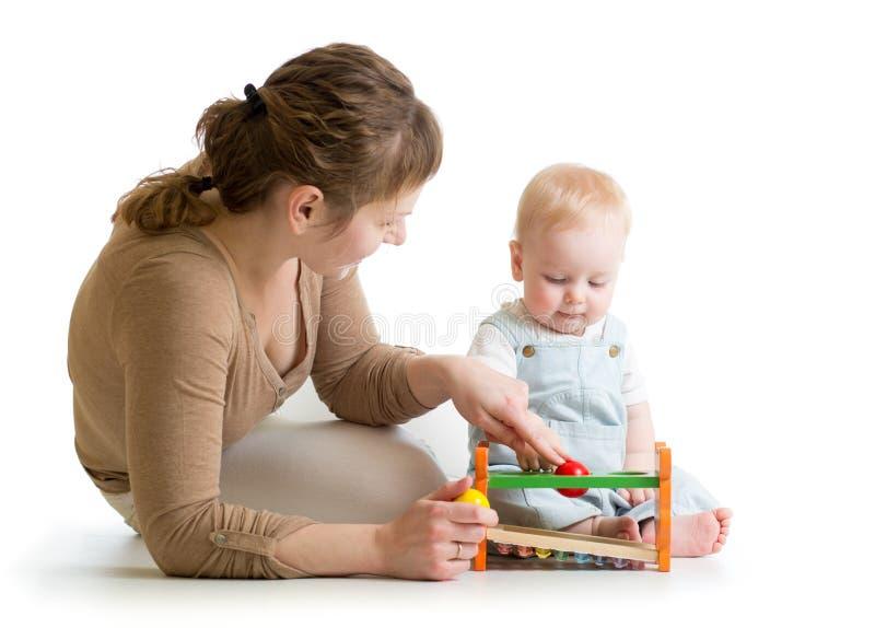 Behandla som ett barn pojken och modern som spelar samman med den logiska leksaken royaltyfri bild