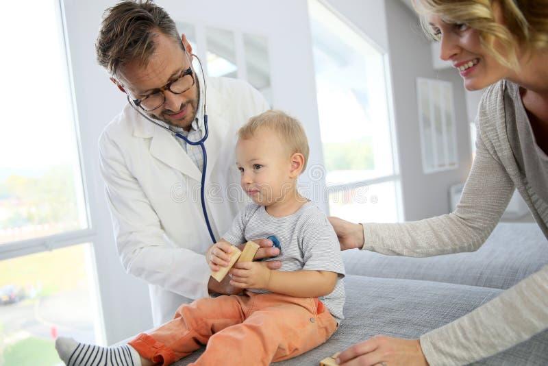 Behandla som ett barn pojken på doktorn som kontrolleras-upp med hans moder arkivfoton