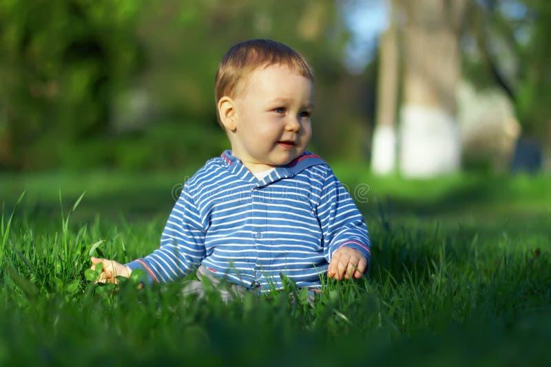 Behandla som ett barn pojken sitter på grönt gräs, fjäderlawn arkivfoto