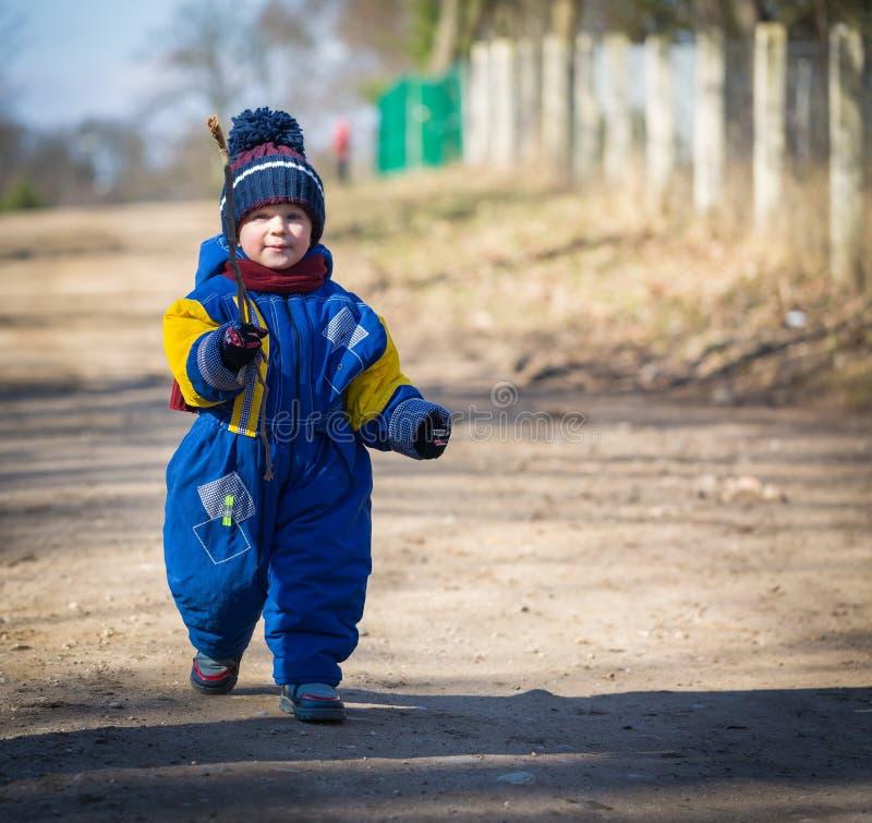Behandla som ett barn pojken som går vid den sandiga lantliga vägen royaltyfri foto