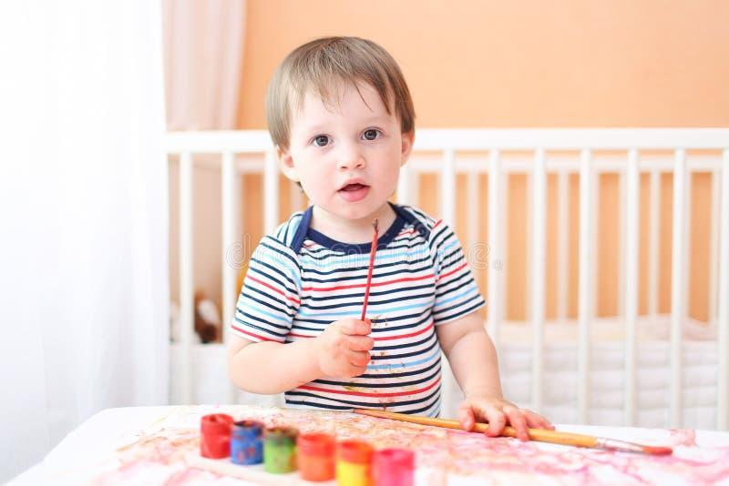 Behandla som ett barn pojken som hemma målar fotografering för bildbyråer