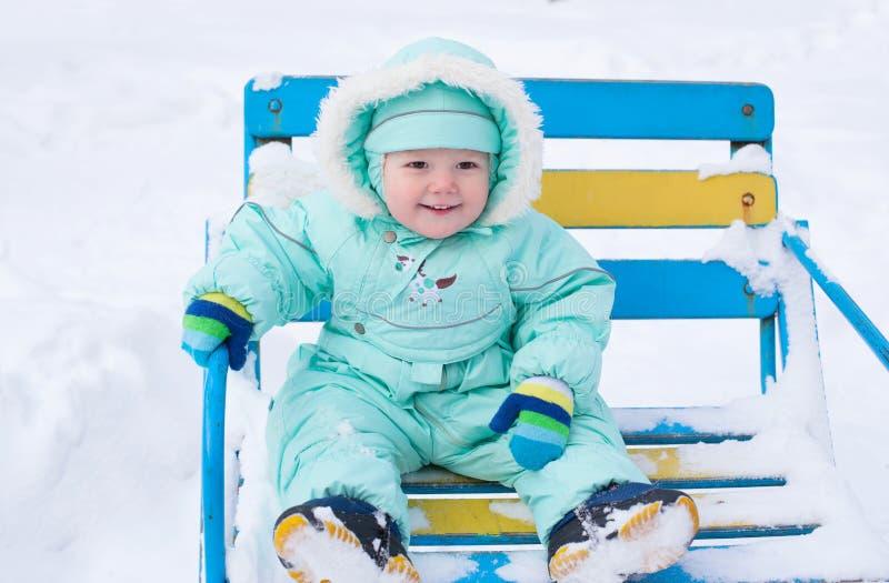 Behandla som ett barn pojken som sammanträde på bänk parkerar in i vinter arkivfoton
