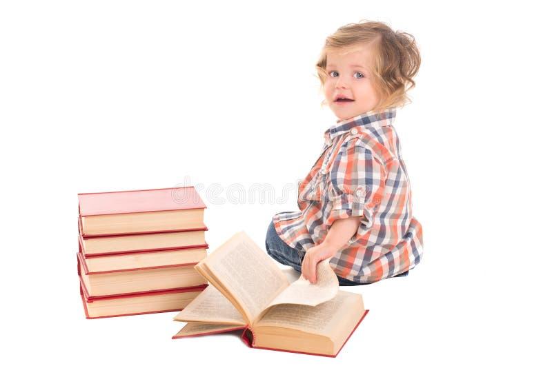 Behandla som ett barn pojken som sitter nära högen av böcker royaltyfri bild