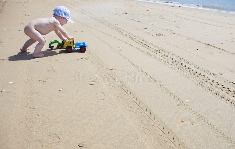 Behandla som ett barn pojken som skjuter hans strandleksaker över sanden royaltyfri fotografi