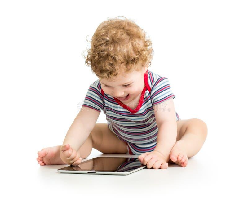 Behandla som ett barn pojken som spelar med den digitala minnestavlan fotografering för bildbyråer