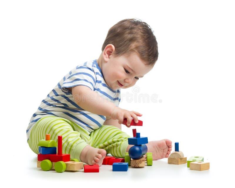 Behandla som ett barn pojken som spelar med kvarterleksaker Isolerat på vit royaltyfria bilder