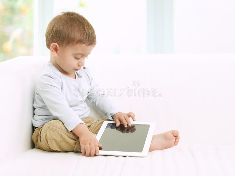 Behandla som ett barn pojken som spelar med minnestavlan royaltyfri fotografi