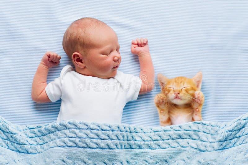 Behandla som ett barn pojken som sover med kattungen Barn och katt arkivfoto