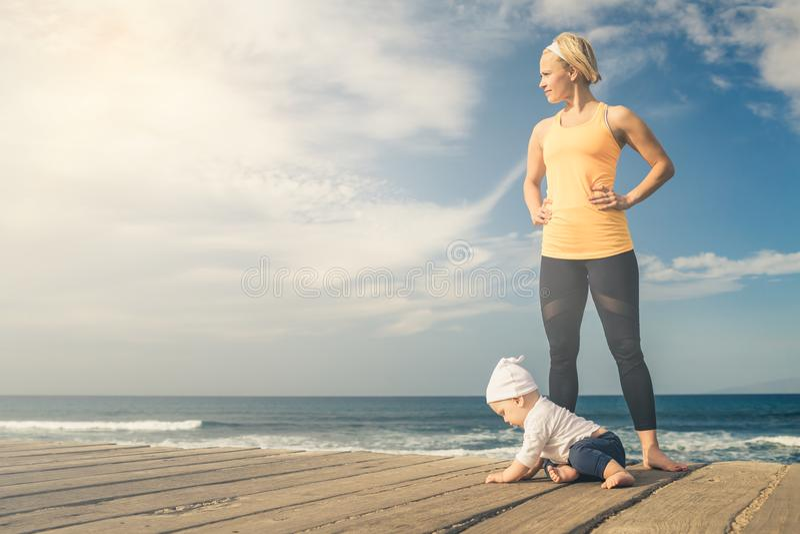 Behandla som ett barn pojken som spelar med modern på stranden, sommardag arkivbilder