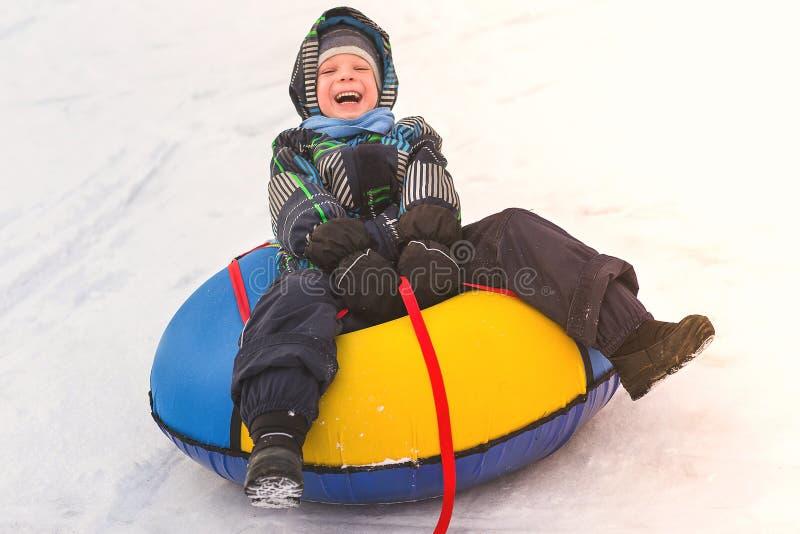 Behandla som ett barn pojkerullningen i den snöig glidbanan på rör Gladlynt stilig pojke som rider en berg-och dalbana fotografering för bildbyråer