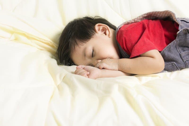 Behandla som ett barn pojkesömn och suga fingret på säng arkivbild