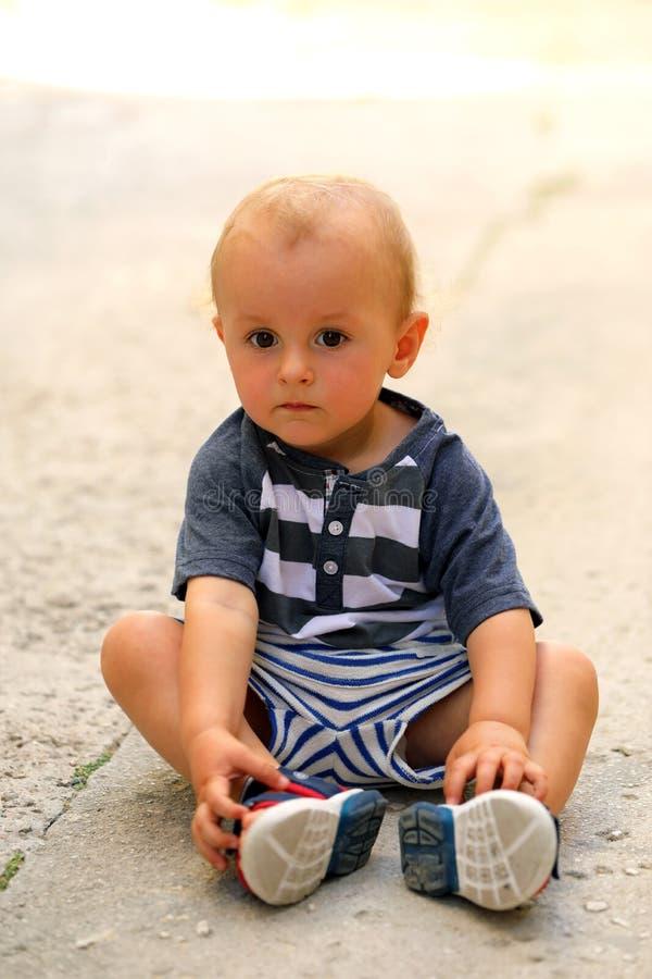 Behandla som ett barn pojkesammanträde på golvet i gatan fotografering för bildbyråer