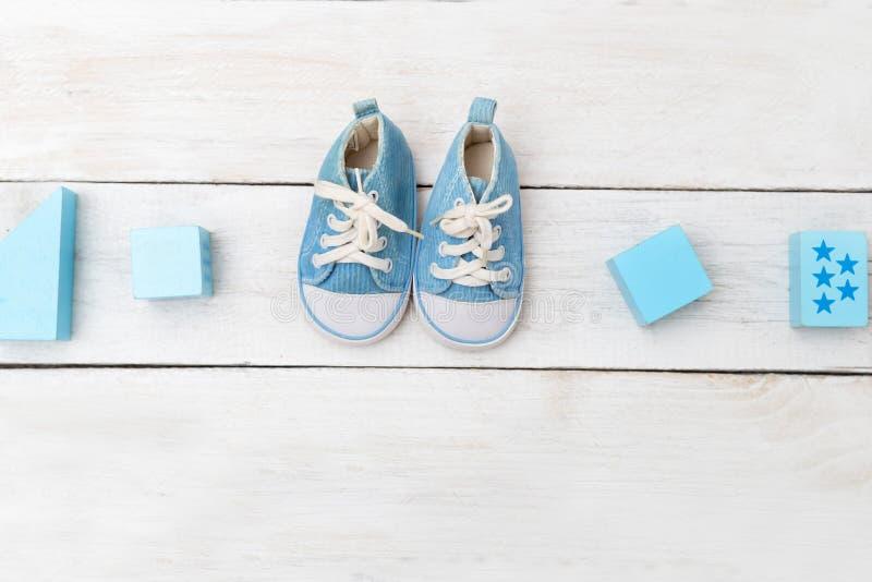Behandla som ett barn pojkeskor och träleksaker på träbakgrund Lekmanna- lägenhet royaltyfri fotografi