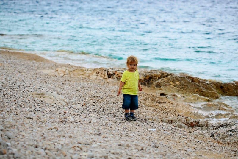 Behandla som ett barn pojkeställningar på stranden arkivbild