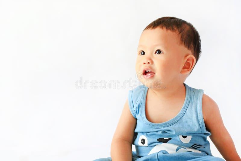Behandla som ett barn pojkeståenden som ser upp på vit bakgrund royaltyfri foto