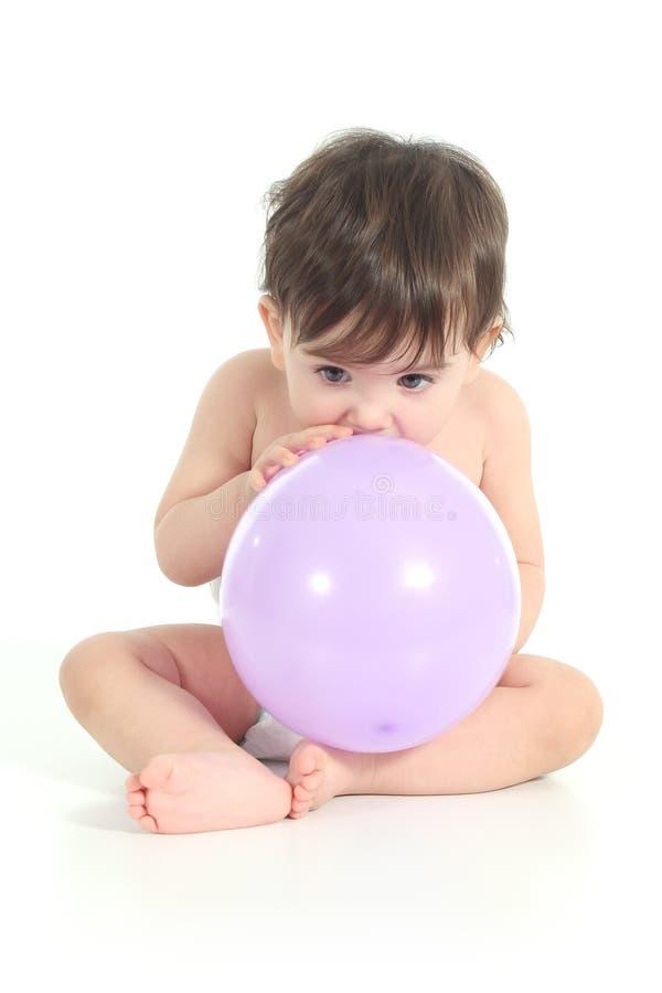 Behandla som ett barn pröva för att inflate en ballong arkivfoto