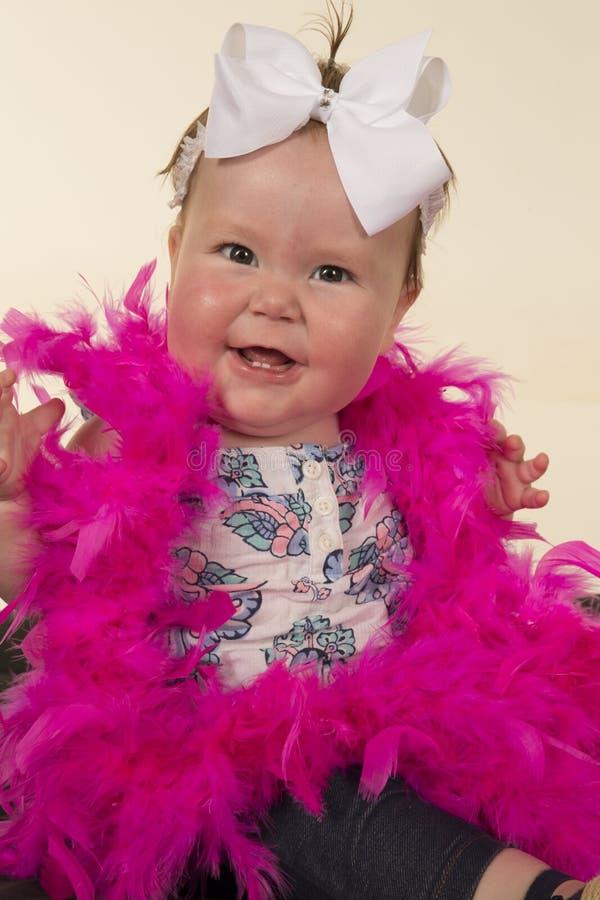 Behandla som ett barn rosa fjädrar för det stora leendet royaltyfri bild