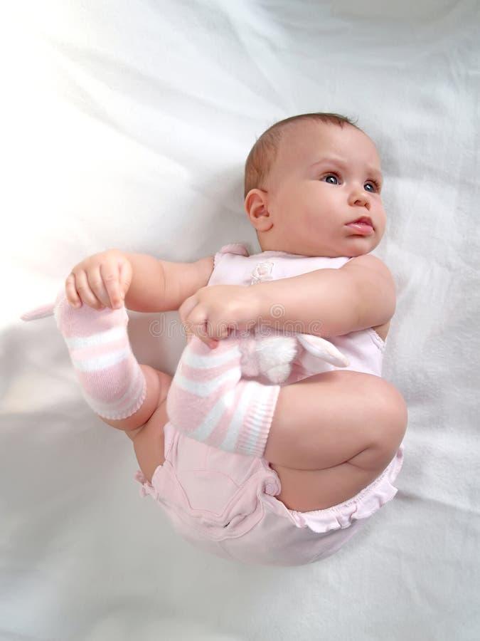 Behandla som ett barn rymmer handfot som ligger på en baksida royaltyfri fotografi