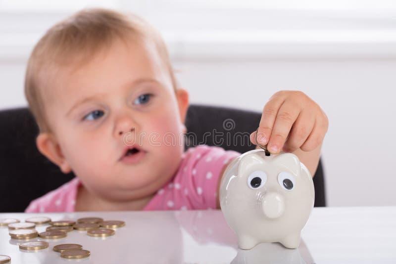 Behandla som ett barn sätta in myntet i Piggybank royaltyfria bilder