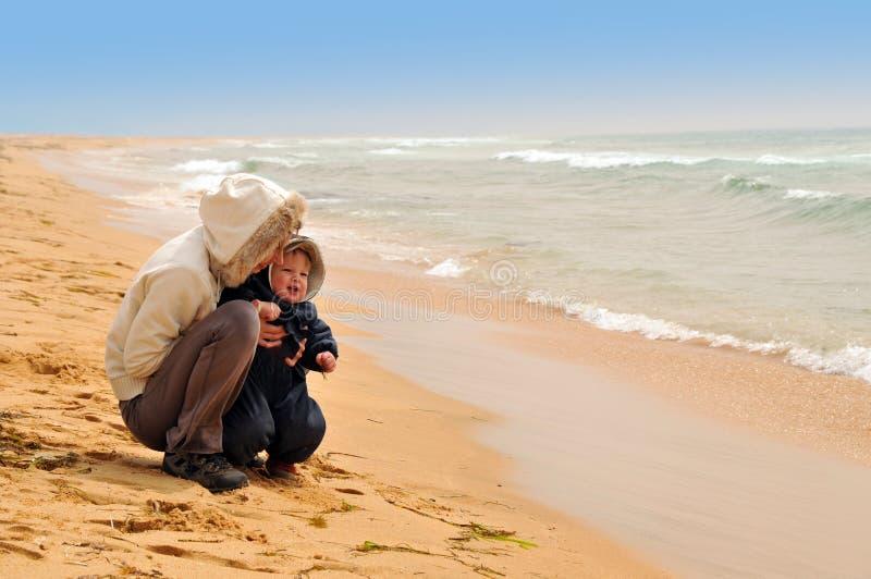 behandla som ett barn sätter på land henne moderhavet arkivbild