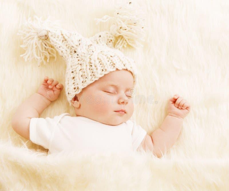 Behandla som ett barn sömn, den nyfödda ungen i Woolen hatt som sover på den vita filten fotografering för bildbyråer