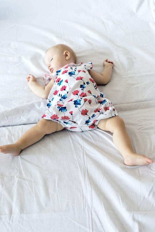 Behandla som ett barn sömnar på ett nyfött vitt ark, liten flicka avverkar sovande på sängen royaltyfri bild
