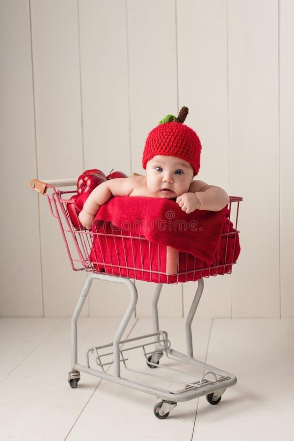 Behandla som ett barn sammanträde i en shoppingvagn som bär en Apple hatt royaltyfri bild