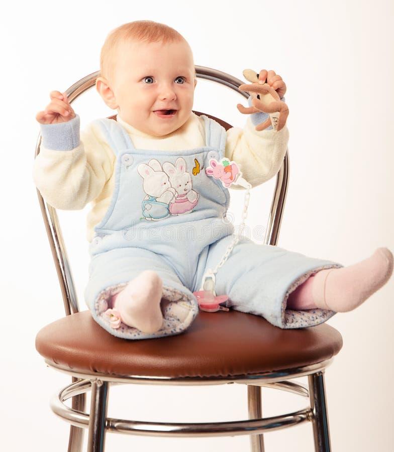Behandla som ett barn sammanträde på en stol, studio royaltyfri foto