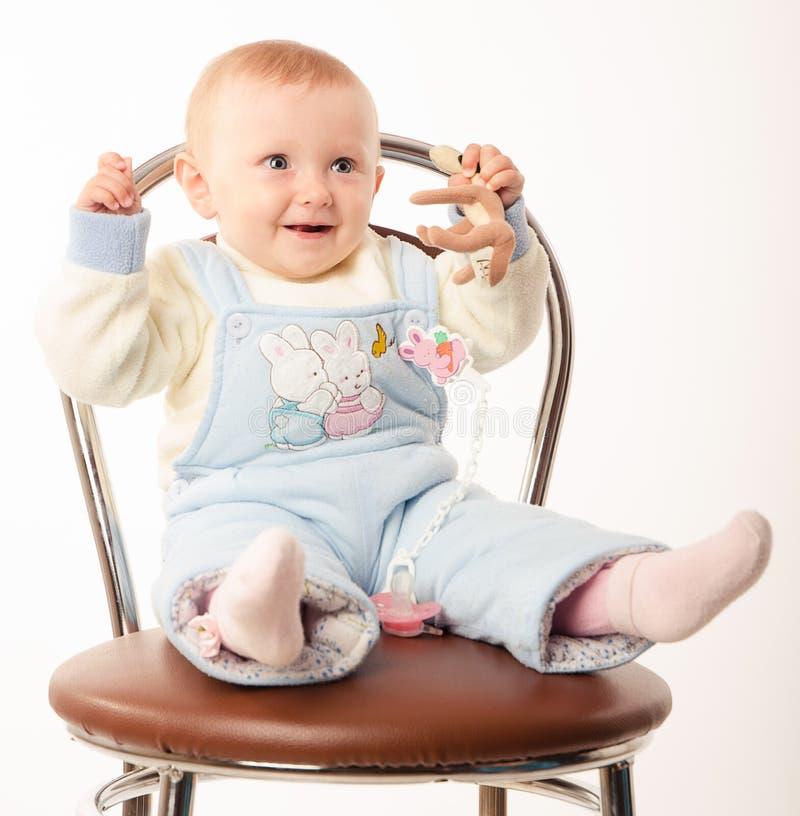 Behandla som ett barn sammanträde på en stol, studio royaltyfria bilder