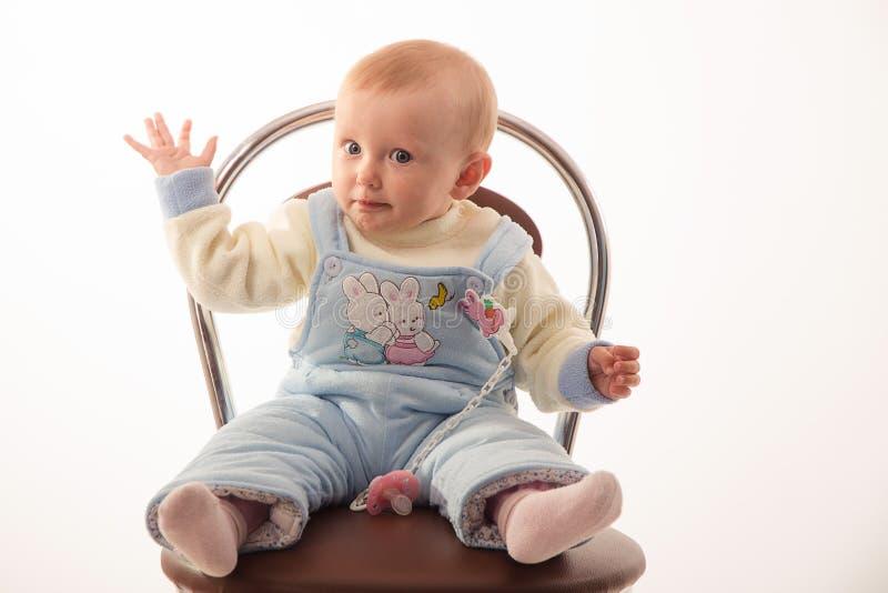 Behandla som ett barn sammanträde på en stol, studio arkivbild